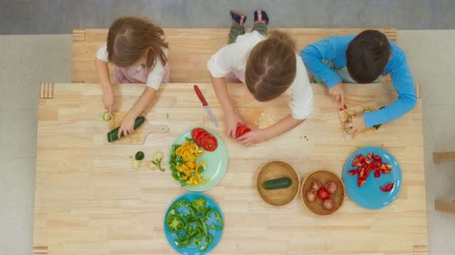 LD Three children cutting vegetables by themselves