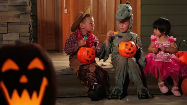 three children in halloween costumes sitting on porch - halloween 個影片檔及 b 捲影像