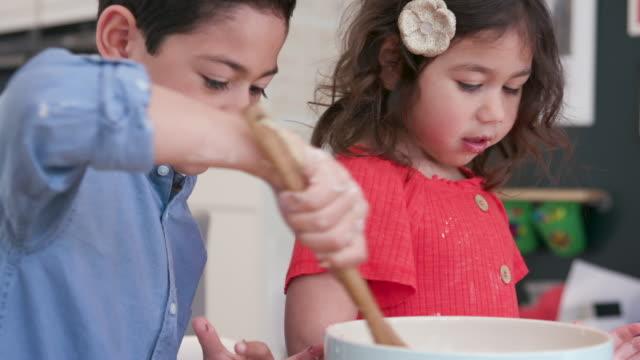tre barn som gör tårtor tillsammans i köket - videor med baka bildbanksvideor och videomaterial från bakom kulisserna