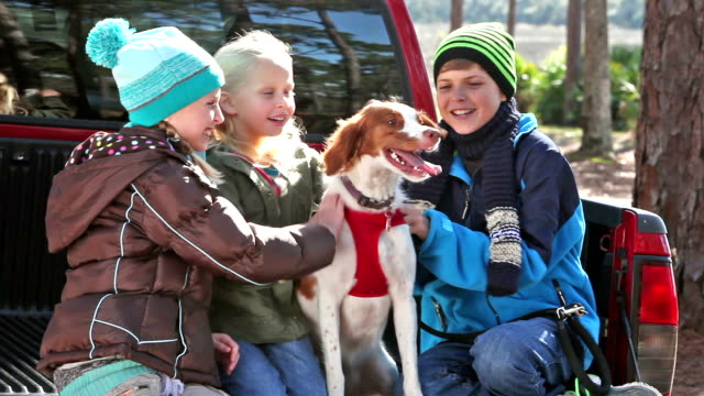 Three children petting their dog, a brittany spaniel
