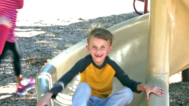 Three children sliding down slide on playground video