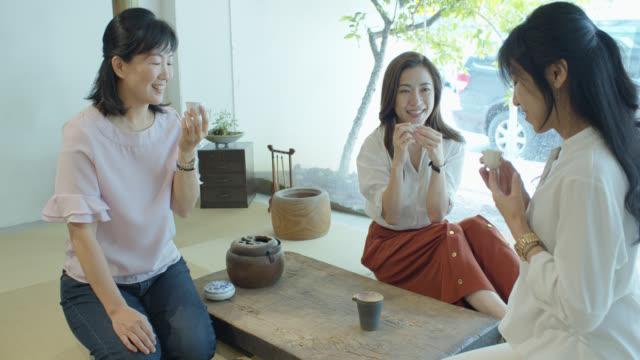 stockvideo's en b-roll-footage met drie chinese vrouwen zittend op tatami het nemen van thee - drie personen