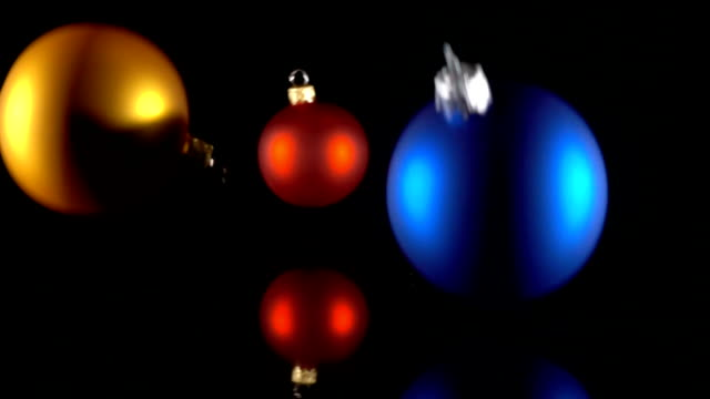 Three christmas balls falling on black background video