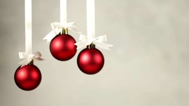 Three Christmas decoration balls falling one by one