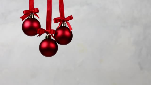 three christmas decoration balls falling one by one - wisieć filmów i materiałów b-roll