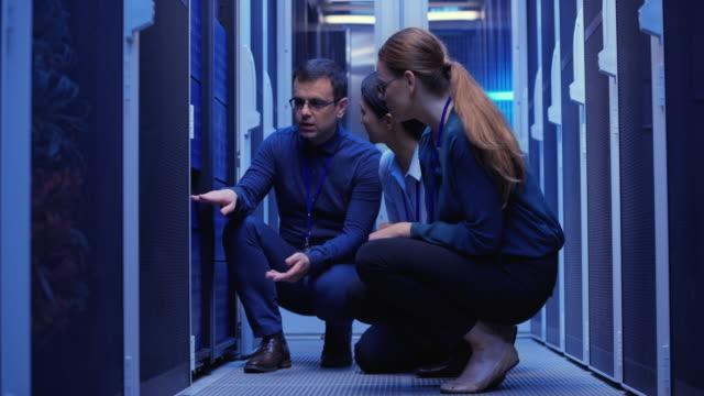 stockvideo's en b-roll-footage met drie collega's crouching door de server in de serverruimte en probleemoplossing - datacenter
