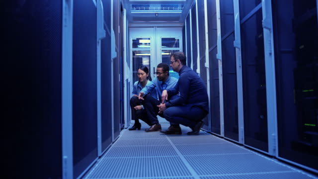 Three colleagues crouching by the servers in the server room and checking for a solution Wide dolly shot of two male and a female sysadmins crouching in the server room and checking the server trying to troubleshoot the reported problem. Shot in Slovenia. server room stock videos & royalty-free footage