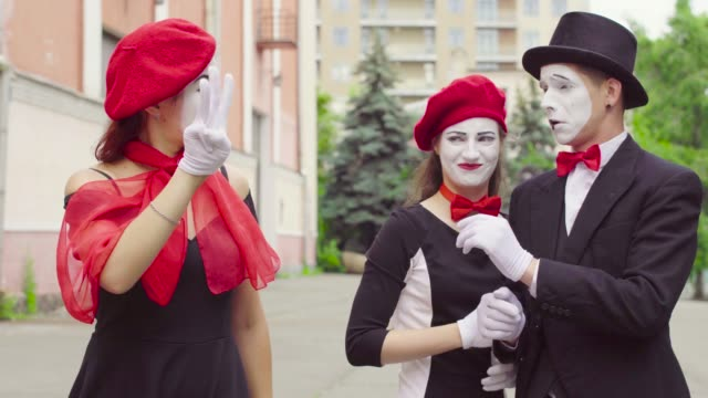 Three comic mimes act in the city street Three funny mimes act in the city street. Company of three mimes, man and women in black dress do perfomance in the city. greasepaint stock videos & royalty-free footage