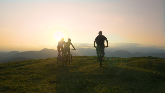 AERIAL: Three cross country cyclists riding up to edge of a hill and high fiving