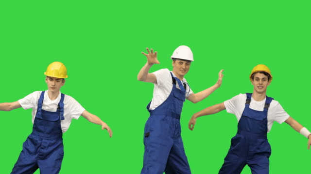 Three dancing construction workers in hard hats on a Green Screen, Chroma Key