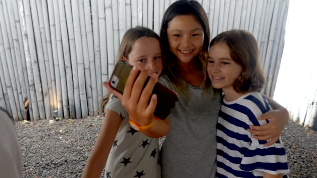 three diverse multi ethnic girl friends taking a selfie with a mobile phone - preadolescente video stock e b–roll