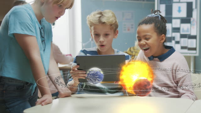 Three Diverse School Children in Science Class Use Digital Tablet Computer with Augmented Reality Software, Looking at Educational 3D Animation Of Solar System. VFX, Special Effects Render