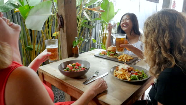 three diverse women laughing and celebrating with drinks and lunch - exotic stock videos & royalty-free footage