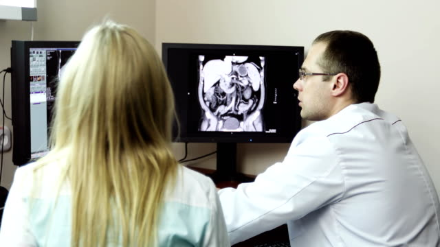 4K Three Doctors analyzing x-ray charts on the PC computer. video
