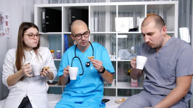 üç doktor staffroom konuşup at break kahve içmelisin. - vitamin d stok videoları ve detay görüntü çekimi