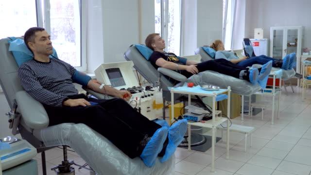 vídeos de stock e filmes b-roll de three donors donating blood plasma in a transfusion center. - blood donation