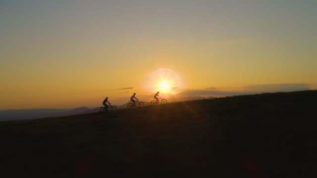 COPY SPACE: Three downhill bikers pedalling their bicycles up a hill at sunrise.