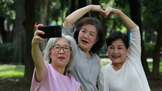Three Elderly Taiwanese Ladies Having Fun Taking Selfies At Park