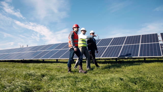 three engineers and solar panels - energia sostenibile video stock e b–roll