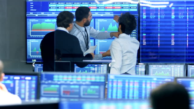 three experienced stock traders talking business, consulting documents and argue about data. they work for a big stock exchange firm. office is full of displays showing infographics and numbers. - professione finanziaria video stock e b–roll