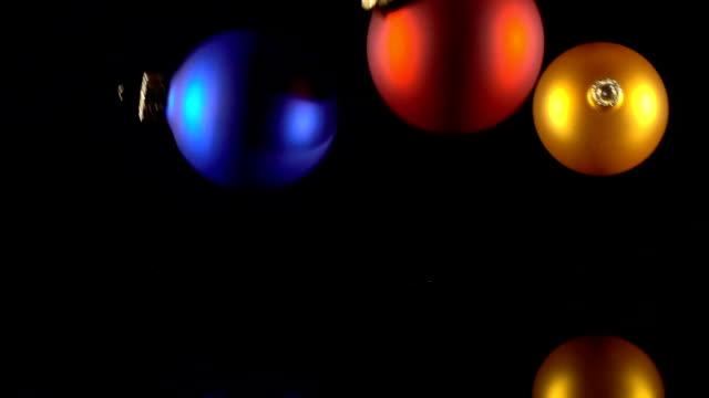 Three falling christmas balls on black background video