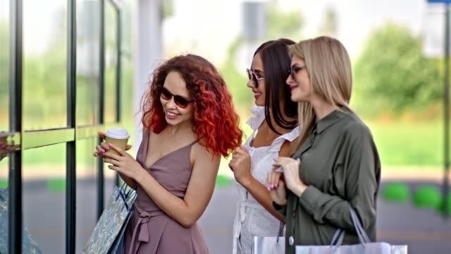 vidéos et rushes de trois ami de femme à la mode avec le sac à provisions désiré regardant la vitrine de fenêtre en verre - désir