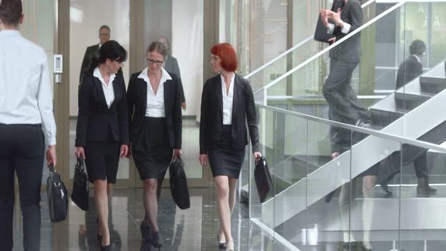 vídeos de stock, filmes e b-roll de businesswomen ds três mulheres conversando e caminhada pelo corredor - saia
