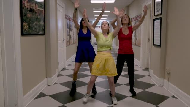 tre kvinnliga dansare dansar en koreograferad dans på ett rutigt golv - blue yellow band bildbanksvideor och videomaterial från bakom kulisserna