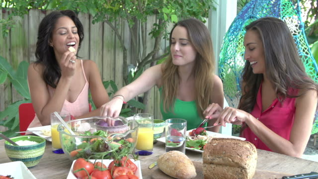 Three Female Friends Enjoying Meal Outdoors At Home video