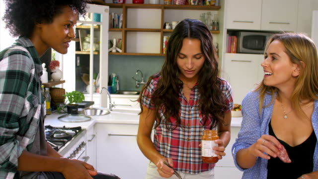 three female friends making pizza in kitchen together - 焗 預備食物 個影片檔及 b 捲影像