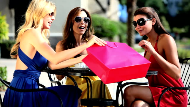 Three female friends meeting at outdoor cafe video