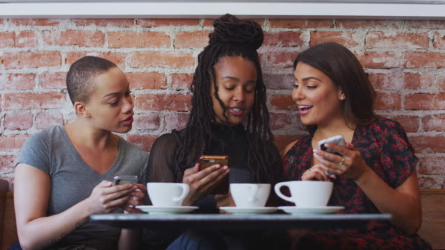 Three Female Friends Meeting For Coffee Sitting At Table Looking At Mobile Phones