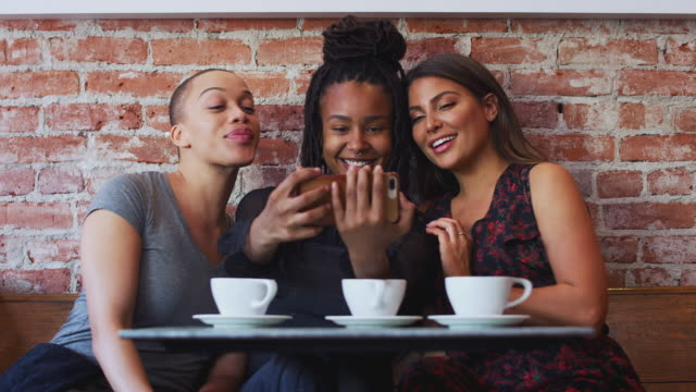 Three Female Friends Meeting For Coffee Sitting At Table Posing For Selfie