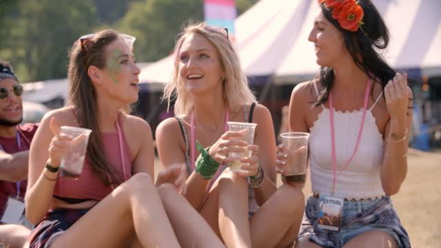 3 female 프렌즈 앉은 grass music festival) 에서 - 전통 페스티벌 스톡 비디오 및 b-롤 화면