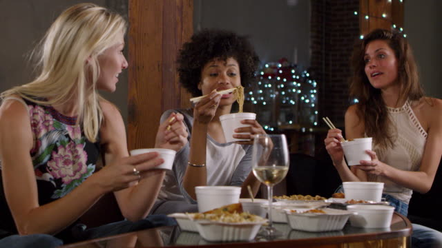 Three female friends talking and eating a Chinese take-away, shot on R3D - vídeo