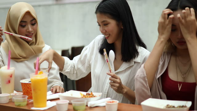 Three Female Friends Tasting Exotic Asian Cuisine