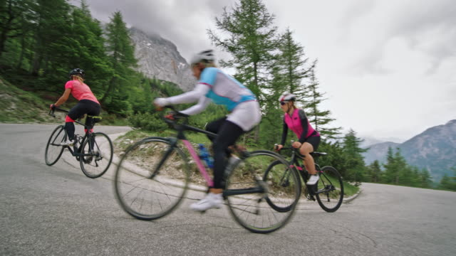 Three female road cyclists riding up the road high in the mountains on a cloudy day