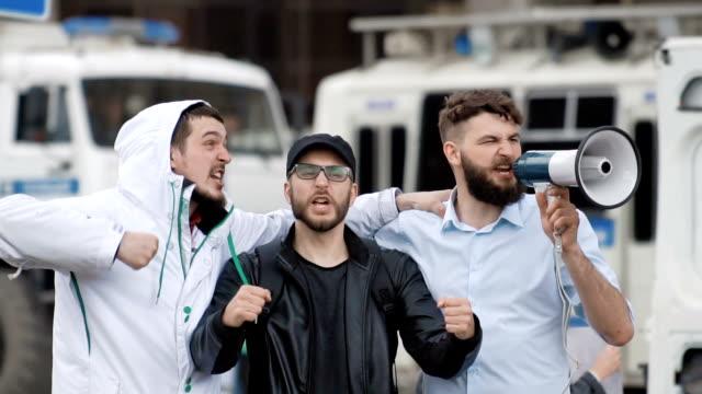 vídeos y material grabado en eventos de stock de feller de fútbol tres en el fondo del coche de policía. los niños griten en un megáfono. - rivalidad