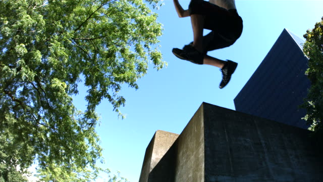 Three free runners jump off concrete wall, slow motion video