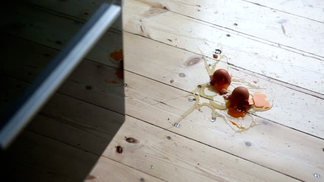 three fresh brown eggs falling on the kitchen floor and making a mess video