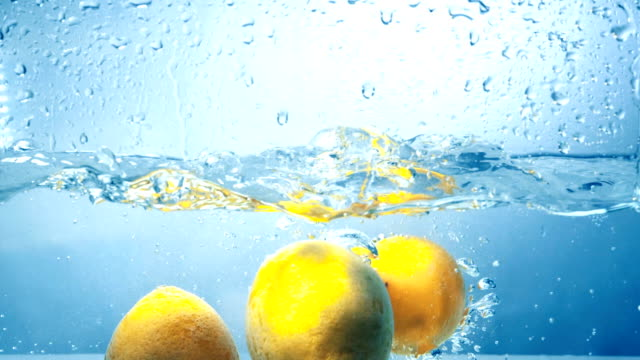 Three fresh lemons fall into water in high contrast shot. video