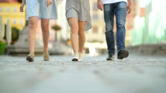 üç arkadaş öğlen kaldırımda yürüyor. onlar are having fun şuna güneşli ve ısı hava - uzun adımlarla yürümek stok videoları ve detay görüntü çekimi