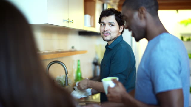 Three friends, black and Hispanic males and white female, meeting in the kitchen video