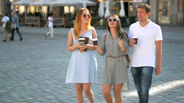 Three Friends Drinking Coffee and Walking around the City During Summer Warm Day. Two Girls Wearing Sunglasses and Short Dresses, Handsome Boy in White Shirt and Jeans Smiling and Talking to Women video