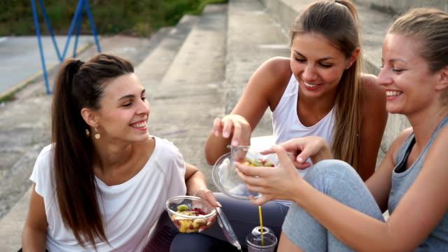 vídeos de stock, filmes e b-roll de três amigos comem a salada de fruta após o treinamento - fruit salad