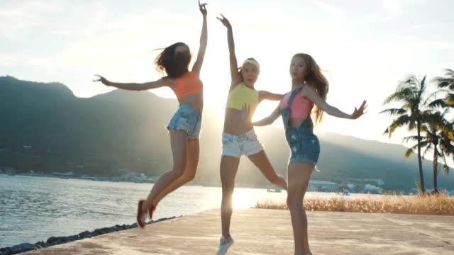 tre vänner hoppa på stranden vid solnedgången. - tjänstekvinna bildbanksvideor och videomaterial från bakom kulisserna