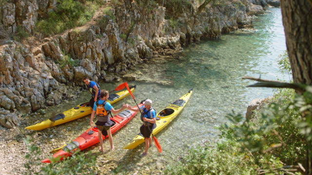Three friends reaching the shore of the sunny bay and stepping out of their kayaks