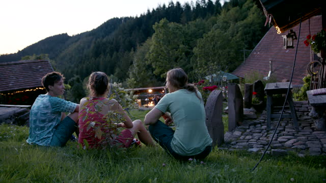 Three friends taking a break outside of a mountain hut at sundown Bikepacking in Germany mid adult stock videos & royalty-free footage