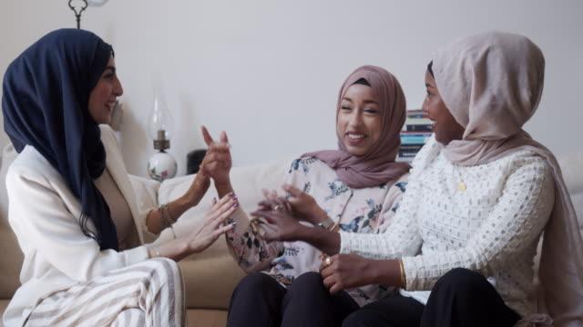 tre vänner pratar tillsammans sitter på soffan hemma - hijab bildbanksvideor och videomaterial från bakom kulisserna