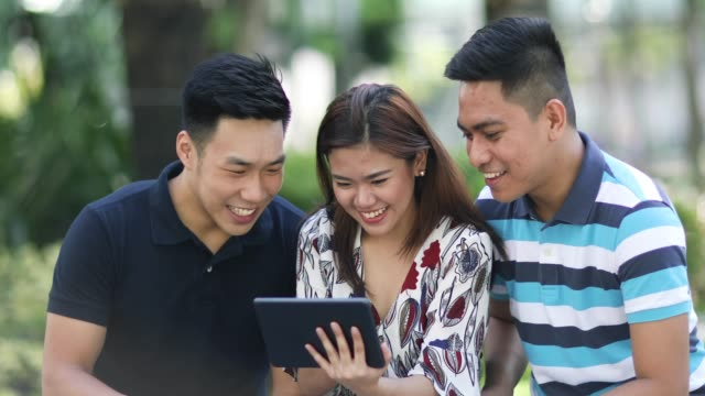 Three friends using a tablet computer Three friends using a tablet computer and playing a game outside in the park. filipino ethnicity stock videos & royalty-free footage